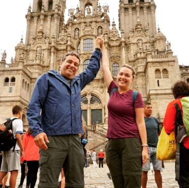 dad and daughter triumphantly posing at the cathedral in Santiago de Compostela, Spain